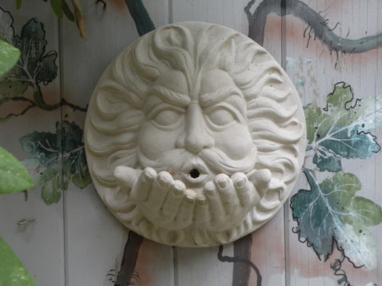 Debbie had part of the tool shed painted with a vine motif, and added this ceramic representation of one of the four winds from classical mythology.